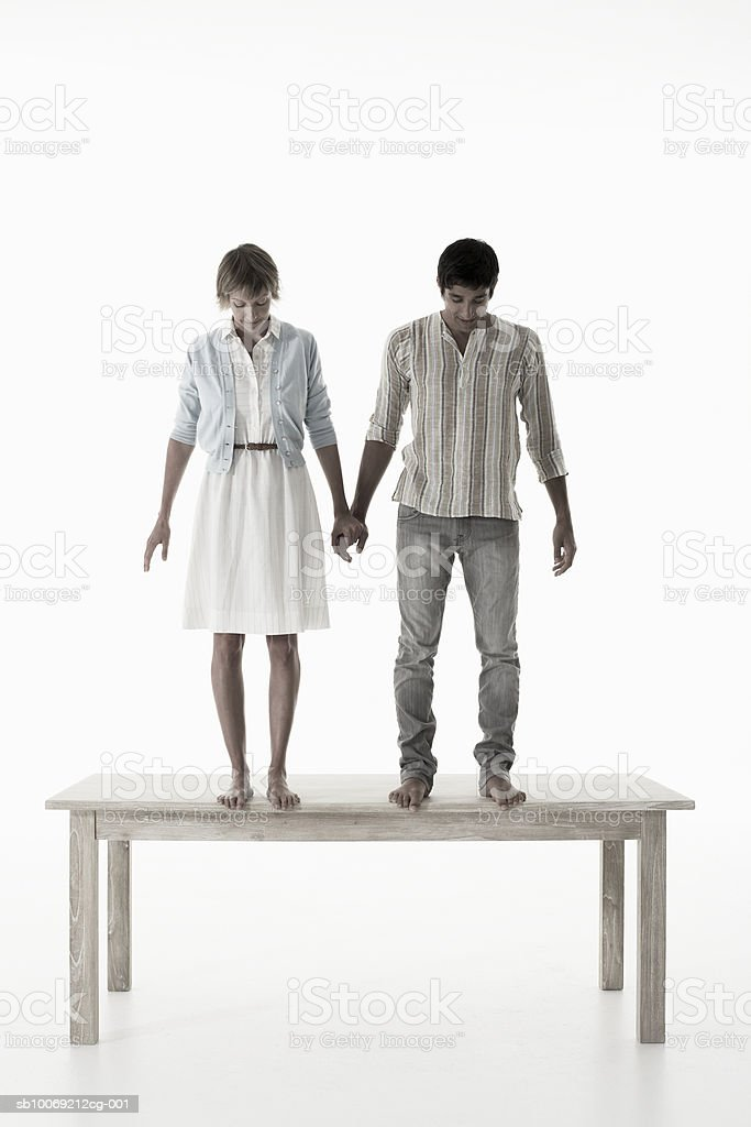 Couple holding hands standing on wooden table against white background royalty-free stock photo