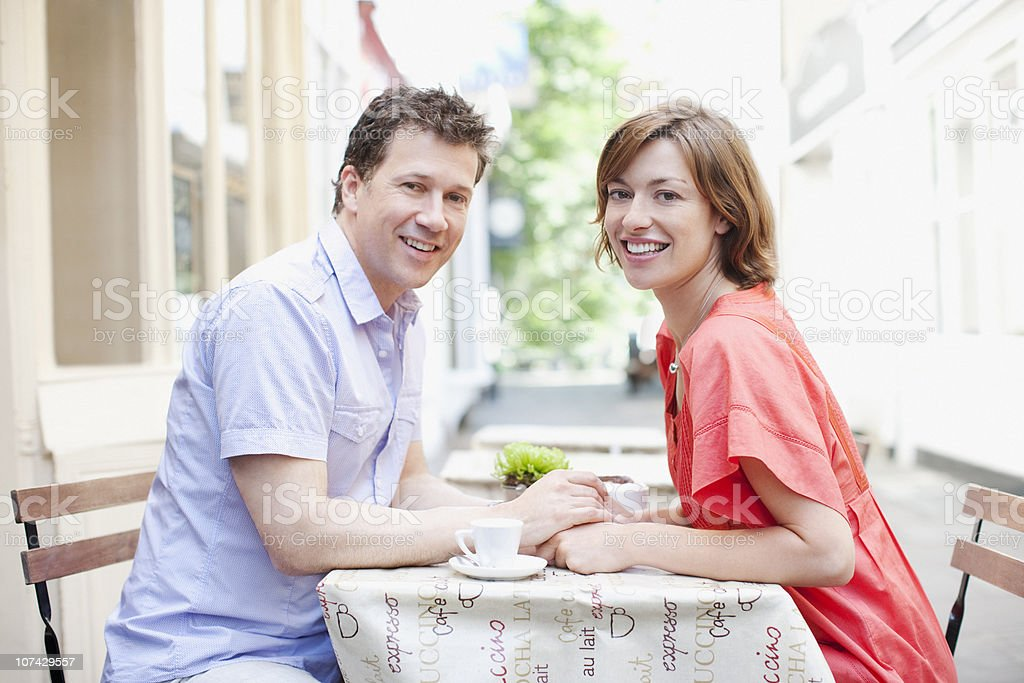 Couple holding hands together in cafe royalty-free stock photo