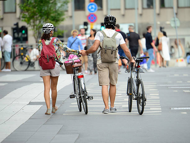 couple holding hands, walking with bikes in city center - stockholm guide stock-fotos und bilder