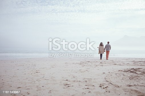 Rear view of happy senior African-American couple walking hand in hand on beach on beautiful day. Authentic Senior Retired Life Concept