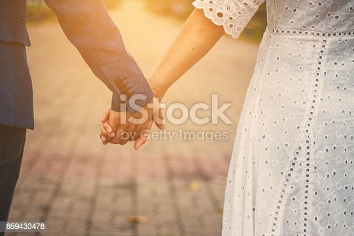 couple holding hands with sunlight  in parkcouple holding hands with sunlight  in park
