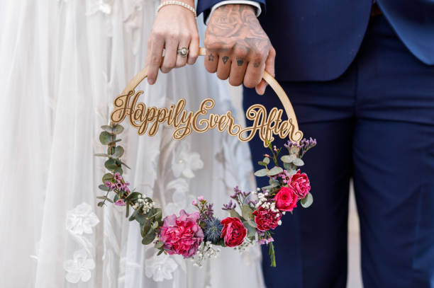 Couple holding Happily Ever After wreath stock photo