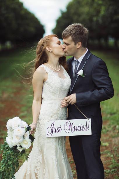 paar holding nur verheiratet zeichen & küssen - heiratssprüche stock-fotos und bilder