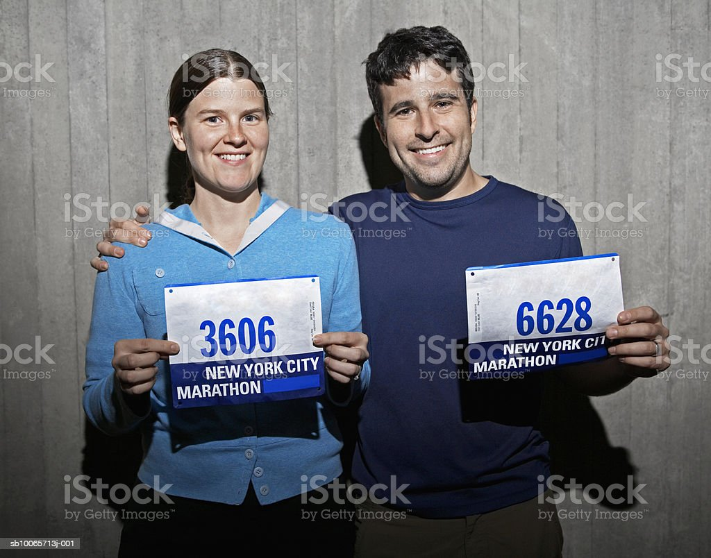 Couple holding marathon numbers, smiling, portrait royalty-free stock photo
