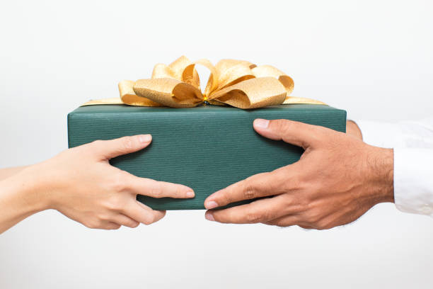 Couple holding packaged Christmas present together stock photo