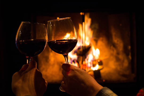 Couple holding pair of glasses with wine at fire pit stock photo