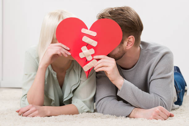 couple holding red paper heart fixed with plaster bandage - chiedere scusa foto e immagini stock