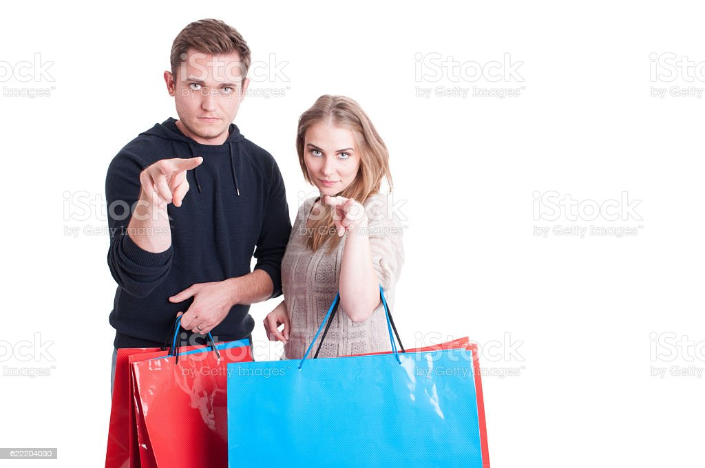 Couple holding shopping bags making watching gesture stock photo