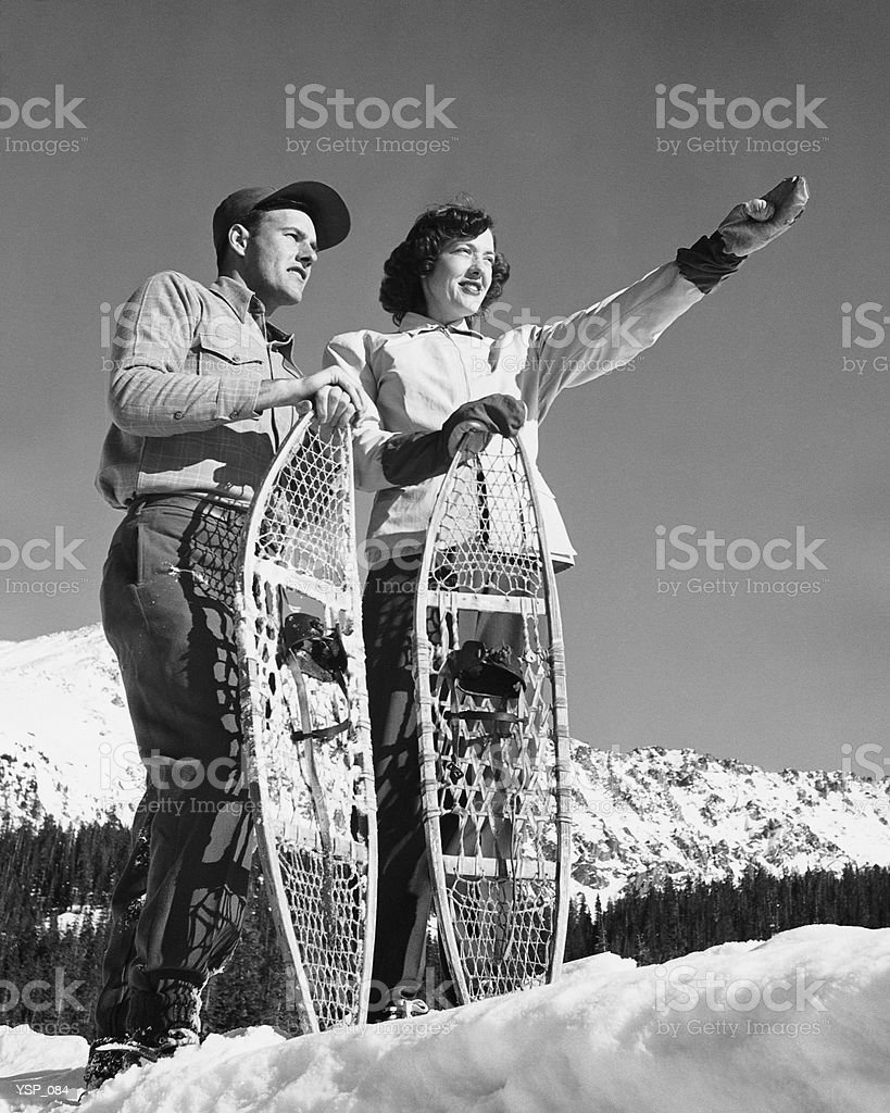 Couple holding snowshoes, woman pointing royalty free stockfoto