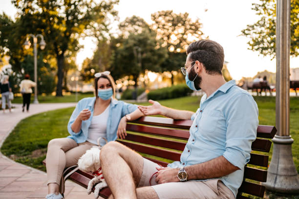 Couple holding social distance on bench stock photo
