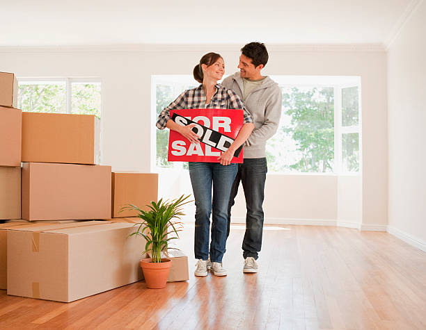 Couple holding sold sign for their new house stock photo