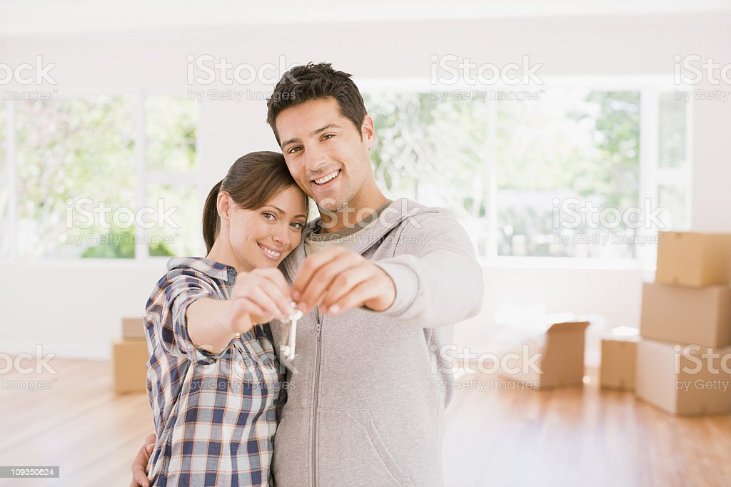 Couple holding the keys to their new house stock photo