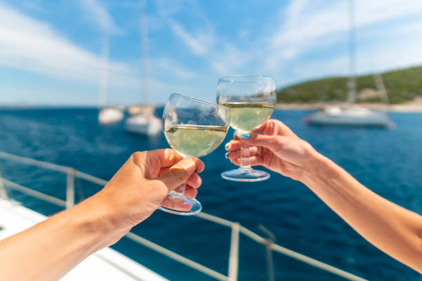 Couple holding two glasses of white wine over ocean background with yacht on background stock photo