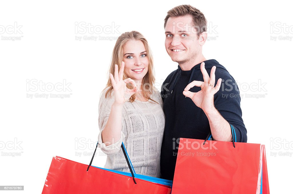 Couple holding up shopping bags making okay gesture photo libre de droits