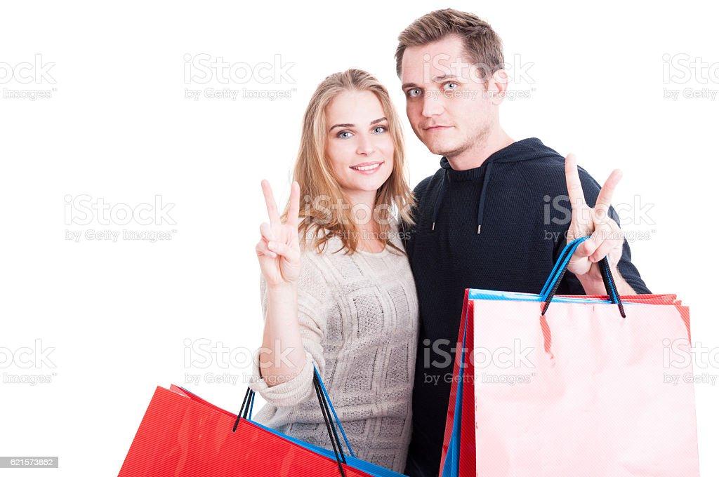Couple holding up shopping bags making peace gesture photo libre de droits