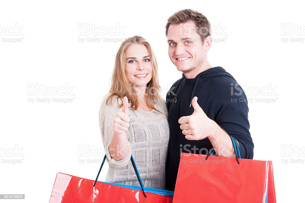 Couple holding up shopping bags making thumb up gesture photo libre de droits