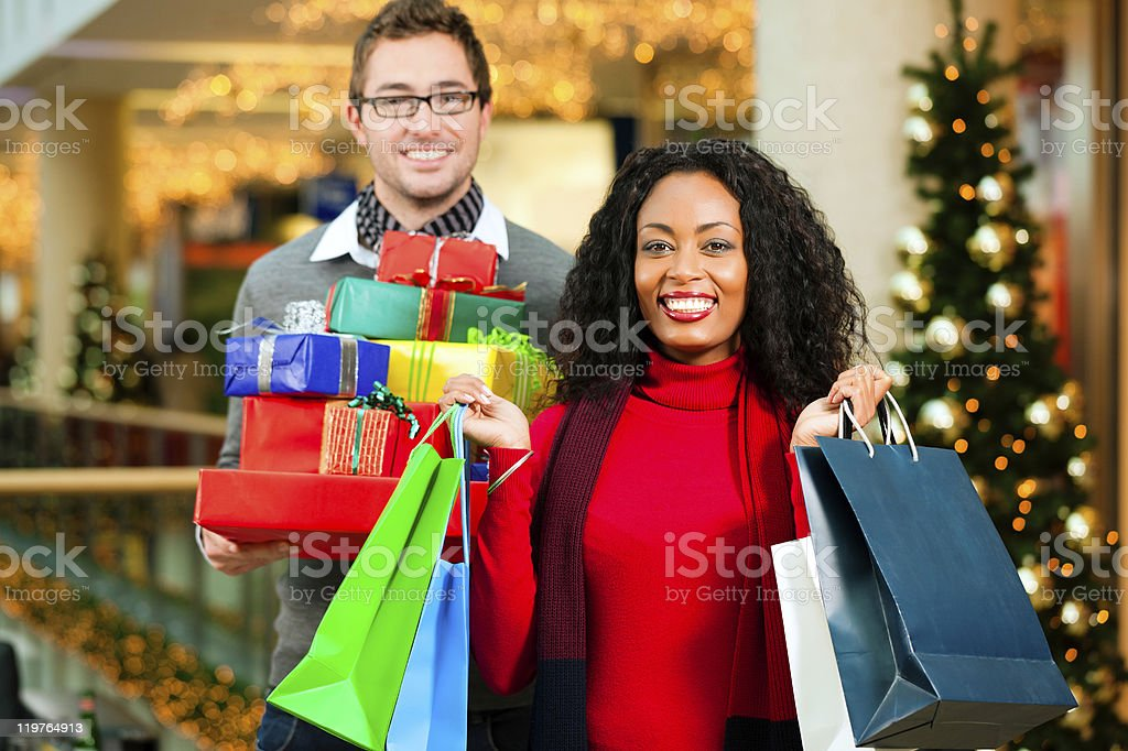 Couple holding wrapped gifts and shopping in holiday setting royalty-free stock photo