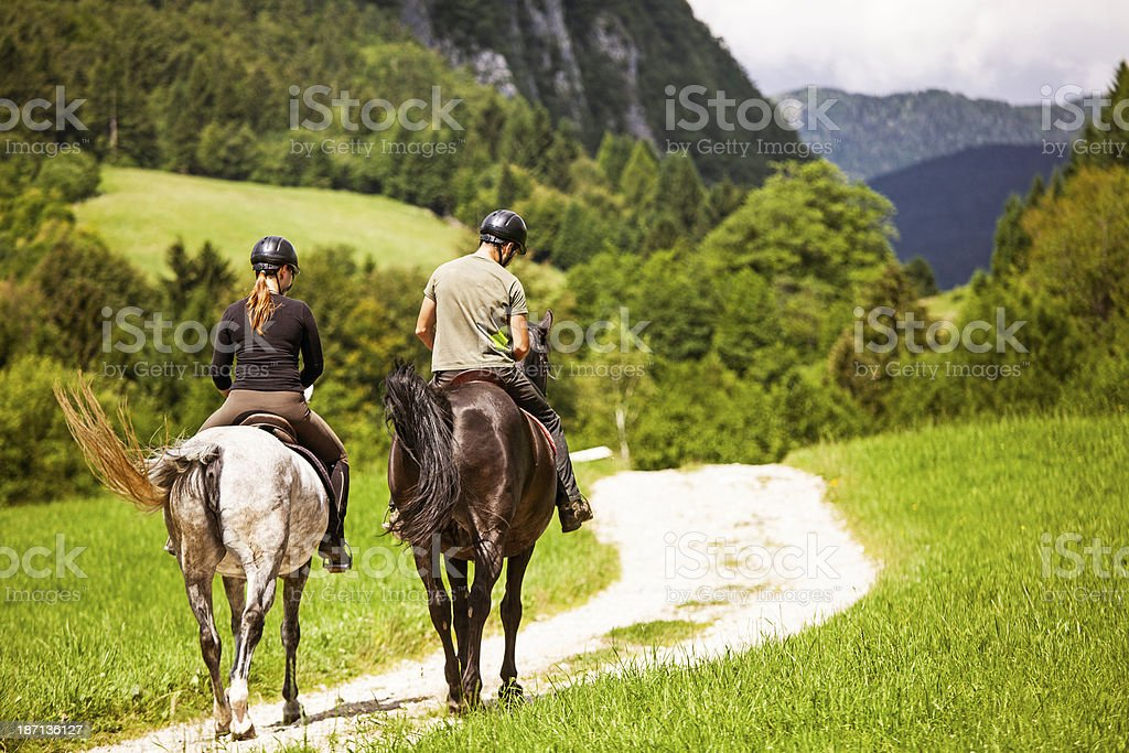 Couple Horseback Riding In The Countryside stock photo
