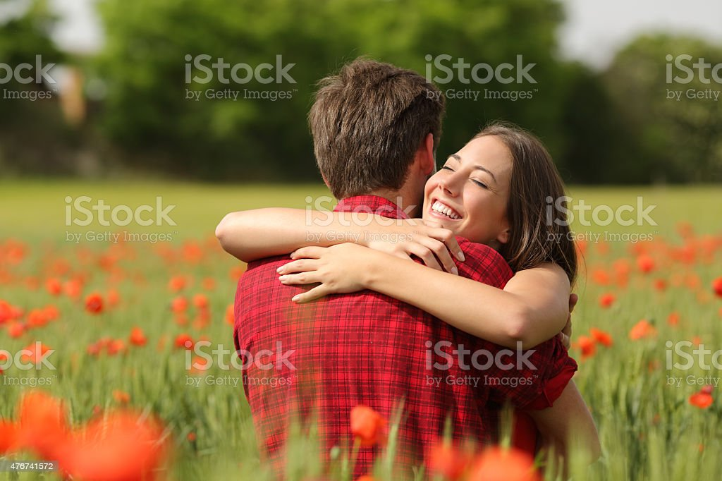 Couple hugging after proposal in a flower field stock photo