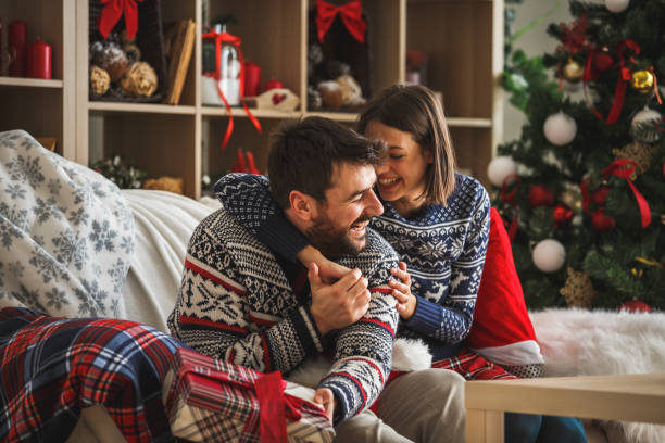 Couple hugging and laughing while enjoying winter holiday at home stock photo
