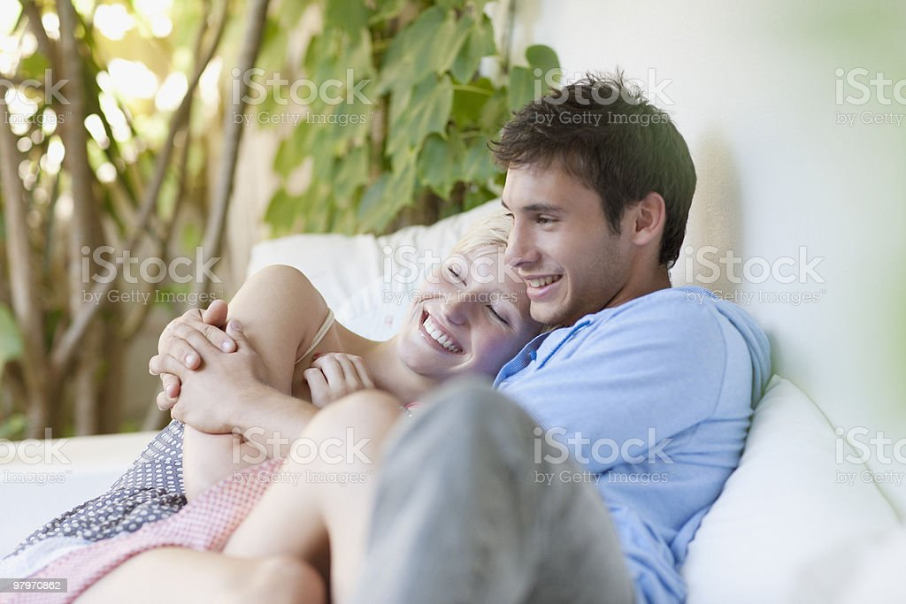 Couple hugging and laying on porch royalty-free stock photo