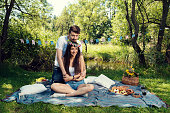 Couple hugging and looking at camera sitting on a blanket in city park She wearing a flower crown Selective focus