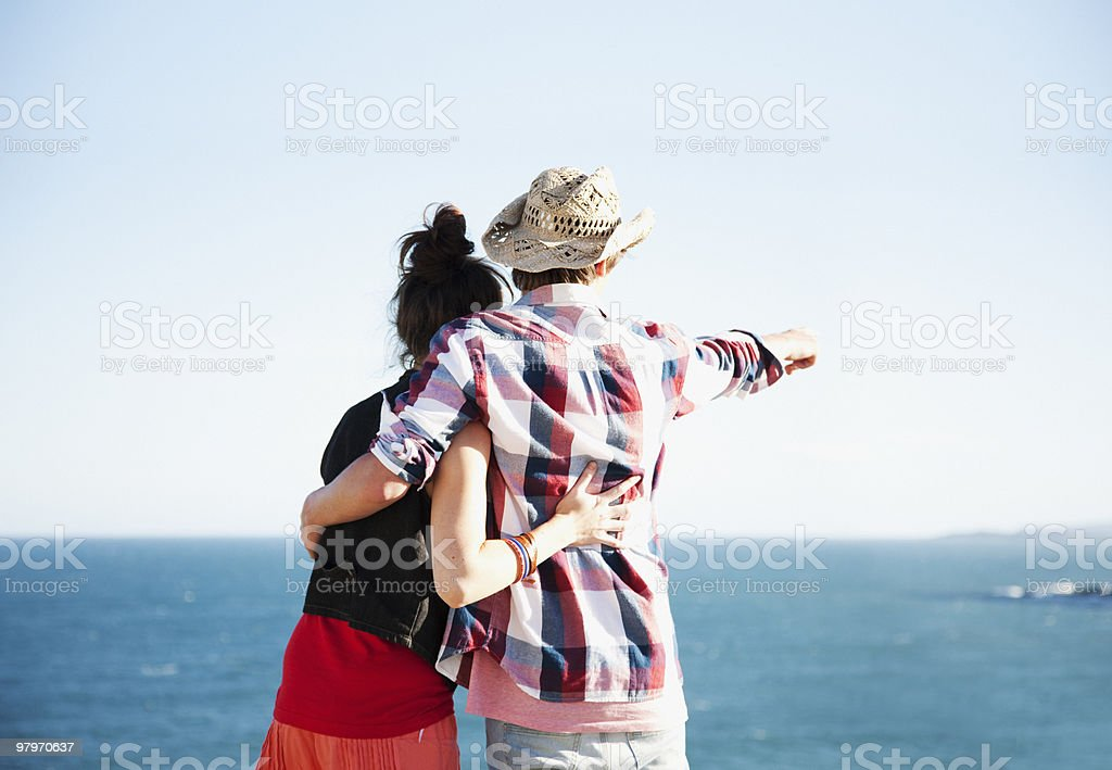 Couple hugging and pointing towards ocean royalty-free stock photo