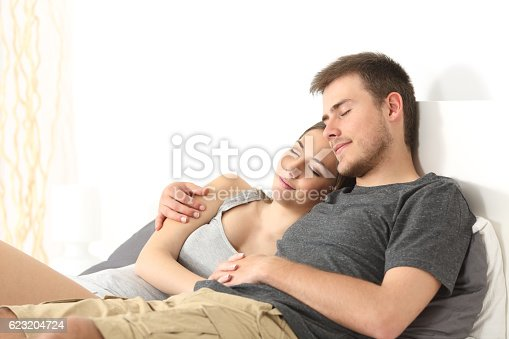 504371332istockphoto Couple hugging and sleeping in a bed 623204724