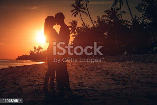 heterosexual couple hugging at sunset