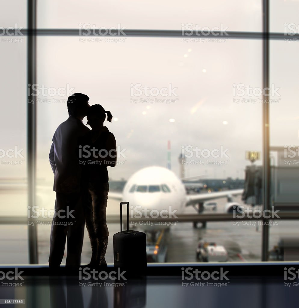 A couple hugging each other at the airport stock photo