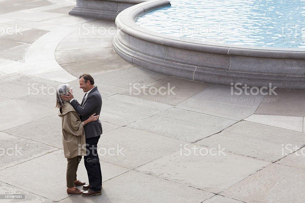 Couple hugging face to face near urban fountain royalty-free stock photo