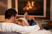 """Young couple hugging on sofa in front of fireplace at home, rear view. Click here for more """"People at Home"""" images:"""
