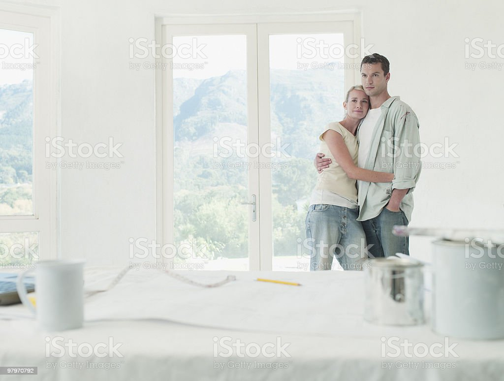 Couple hugging in room with drop cloths and paint cans royalty-free stock photo