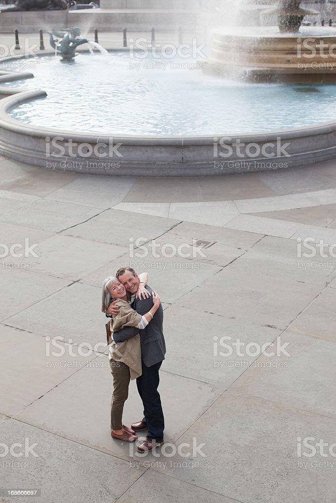 Couple hugging near fountain royalty-free stock photo