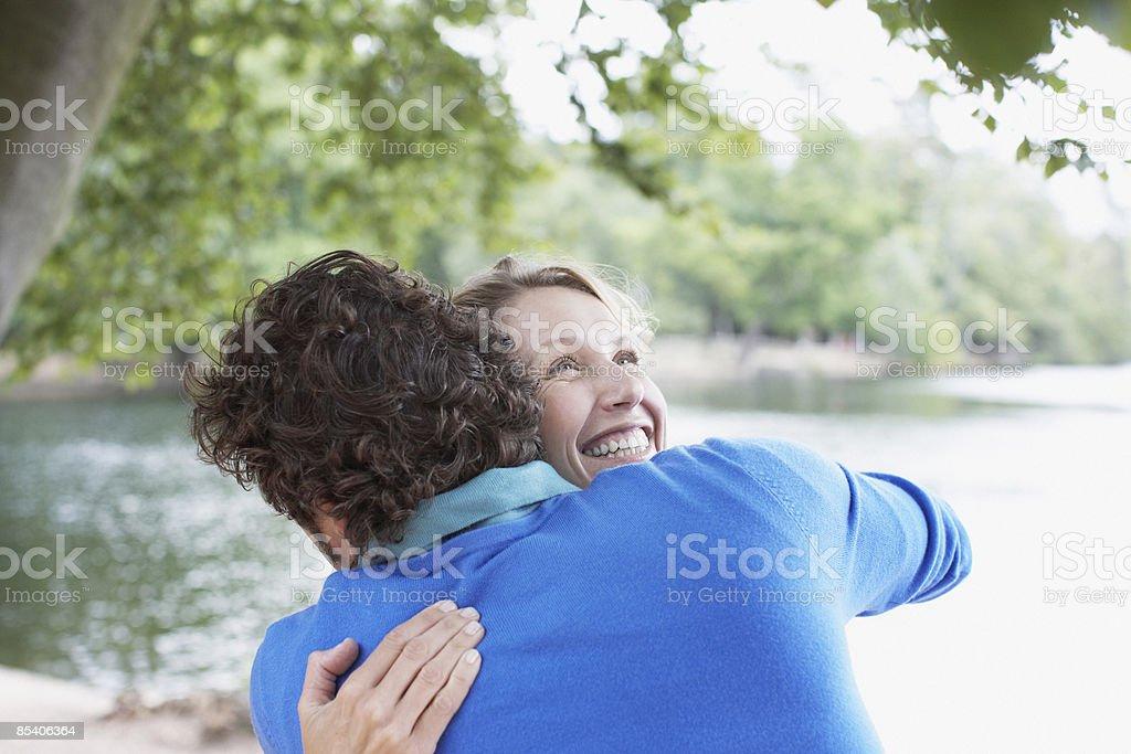 Couple hugging near lake royalty-free stock photo