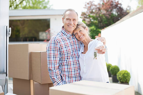 couple hugging near stack of moving boxes - senior housing stock photos and pictures