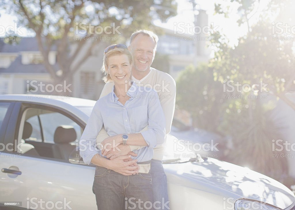 Couple hugging next to car royalty-free stock photo