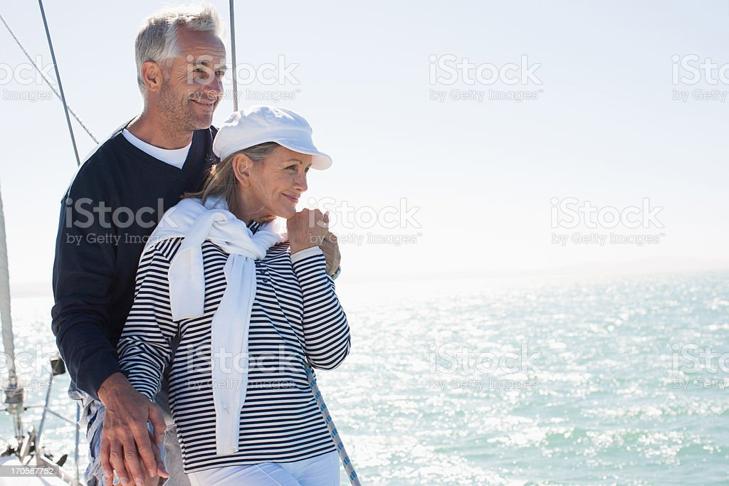 Couple hugging on deck of boat stock photo