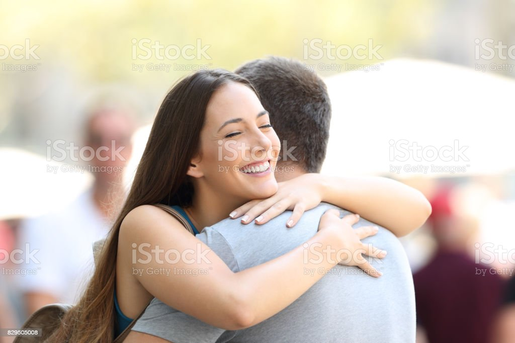 Couple hugging on the street after encounter stock photo