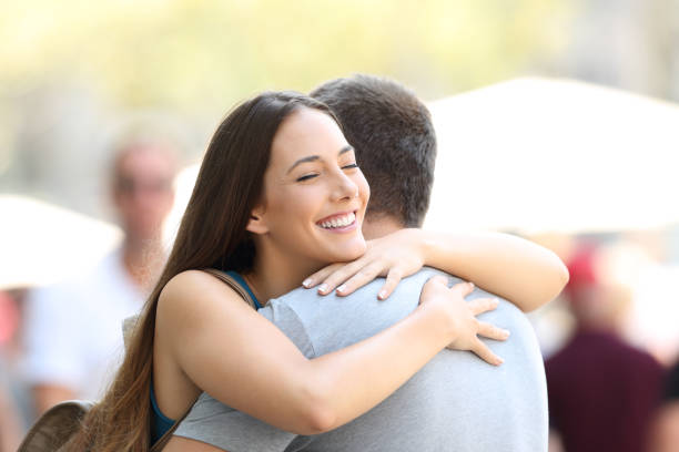 couple hugging on the street after encounter - reunion stock photos and pictures