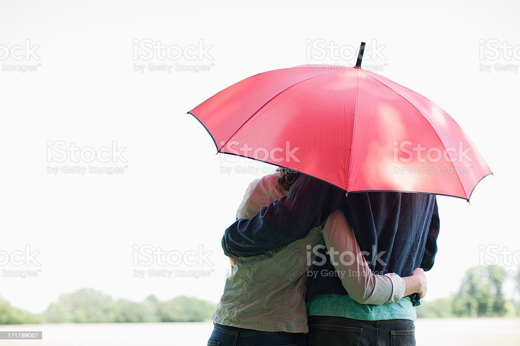 Couple hugging underneath red umbrella stock photo
