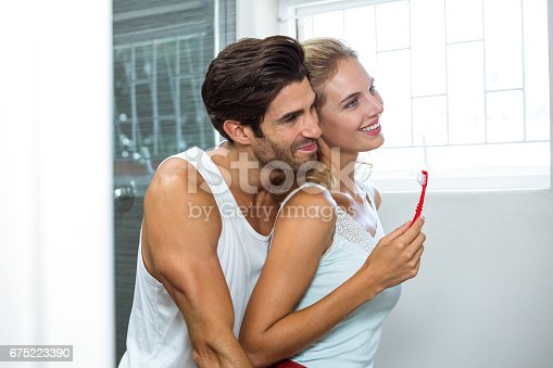 675462768istockphoto Couple hugging while brushing teeth 675223390