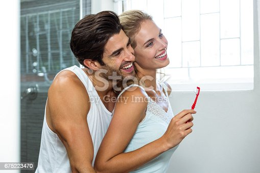 675462768istockphoto Couple hugging while brushing teeth 675223470