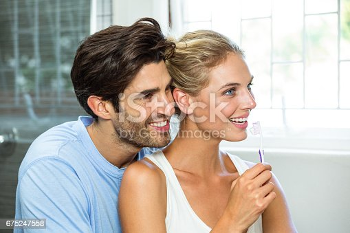 675462768istockphoto Couple hugging while brushing teeth 675247558