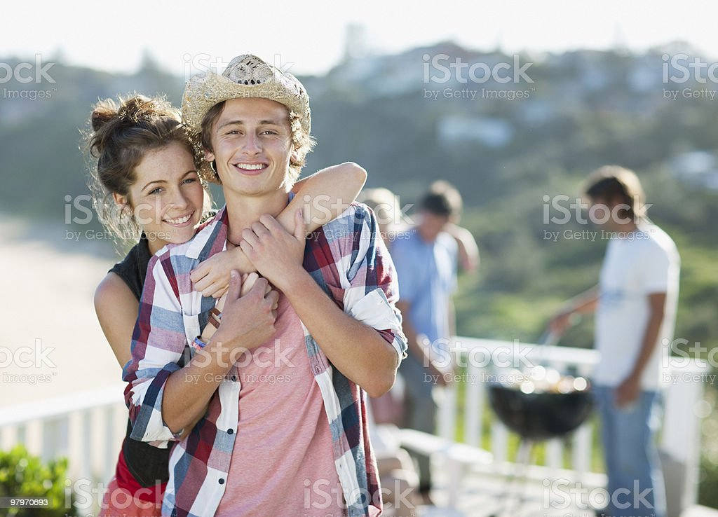 Couple hugging with friends at barbecue in background royalty-free stock photo