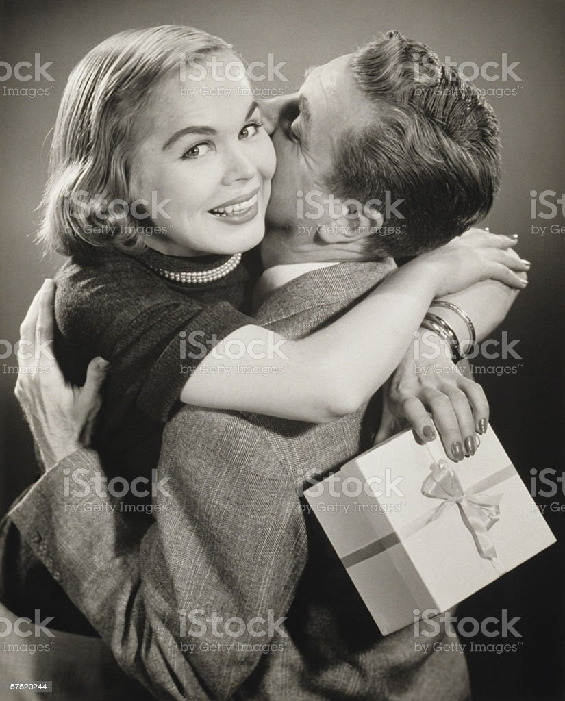 Couple hugging, woman holding gift, (B&W) royalty-free stock photo