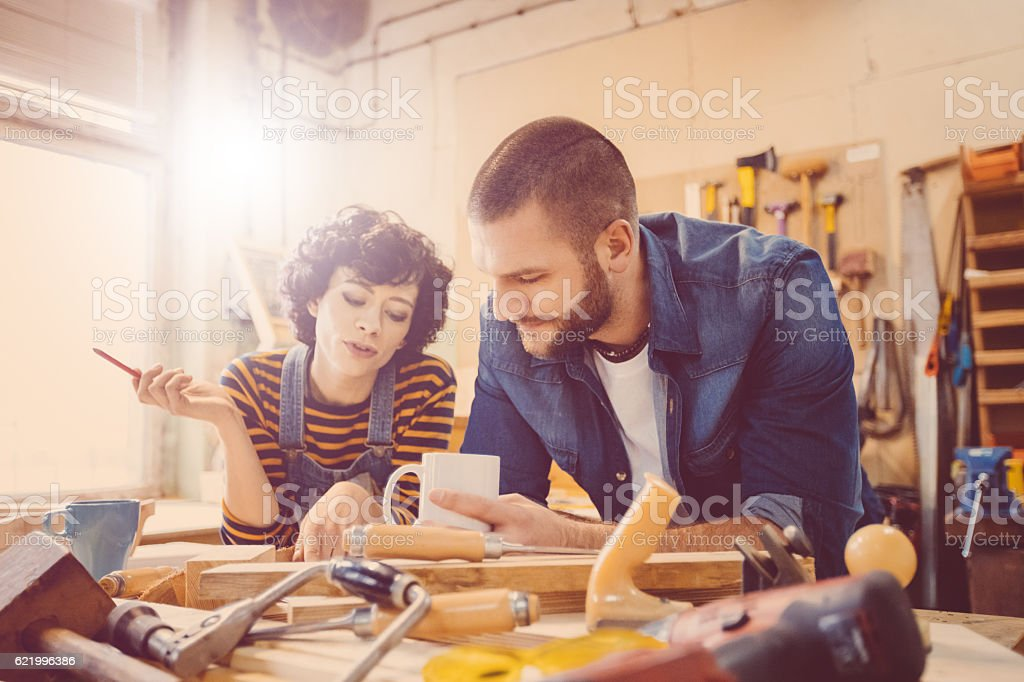 Couple in a construction workshop, learning carpentry stock photo