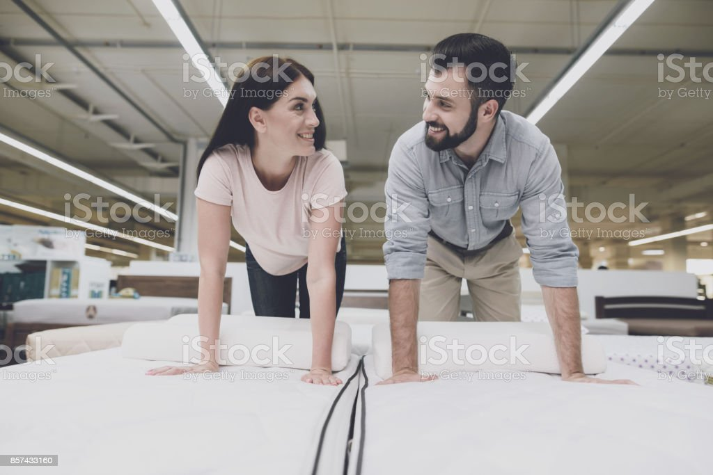 A woman in a light T-shirt and a man in a gray shirt climb onto the...