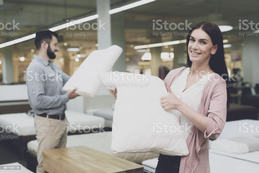 A couple in a large store of beds and mattresses chooses pillows....