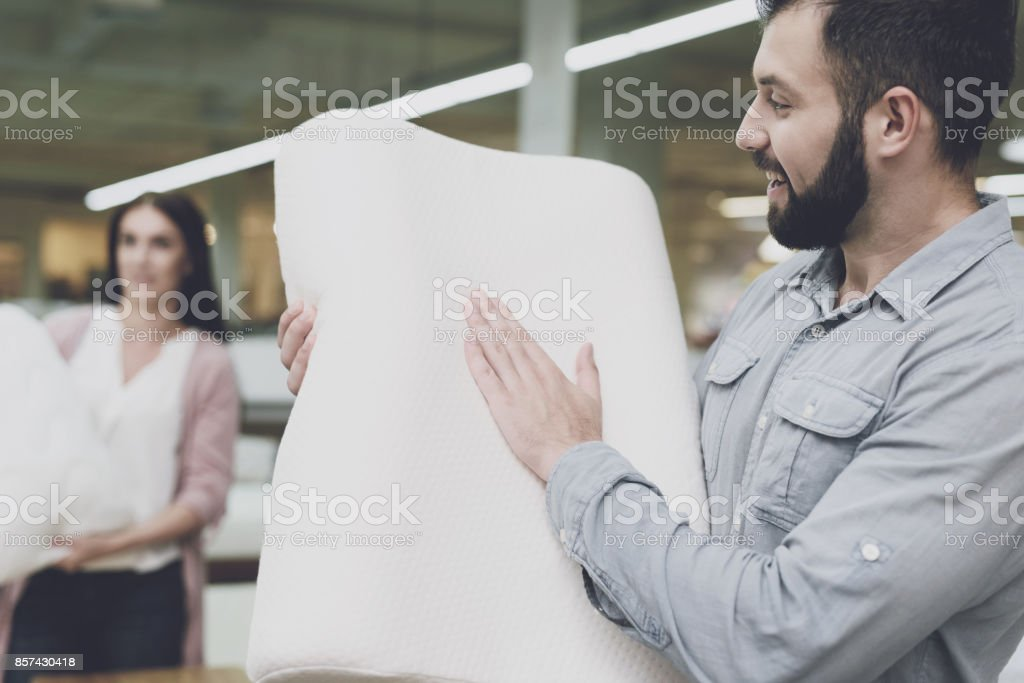 A couple in a large store of beds and mattresses chooses pillows. A...